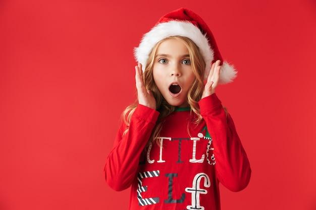 Шокированная маленькая девочка в рождественском костюме стоя изолирована