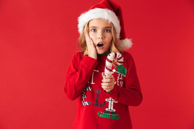 Shocked little girl wearing christmas costume standing isolated
