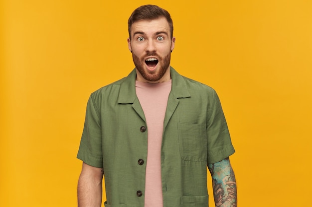 Shocked looking male, handsome guy with brunette hair and beard. wearing green short sleeves jacket. has tattoo and piercing.  with open mouth, isolated over yellow wall