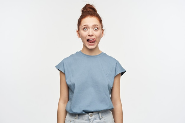 Shocked looking woman, beautiful girl with ginger hair gathered in a bun. wearing blue t-shirt and jeans. lick her lip, shows tongue.  isolated over white wall