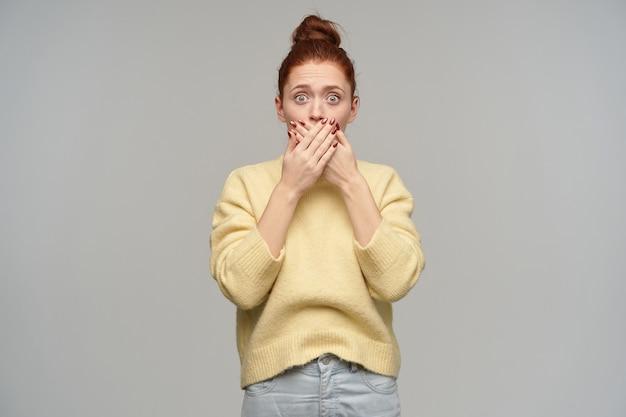 충격적인 찾고 여자, 생강 머리를 가진 아름다운 소녀가 롤빵에 모였습니다. 파스텔 옐로우 스웨터와 청바지를 입고. 손바닥으로 입을 가리십시오. 회색 벽 위에 절연