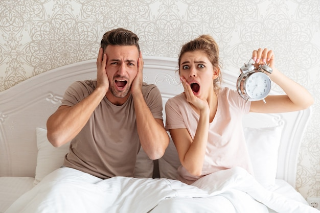 Shocked lovely couple sitting together on bed with alarm clock