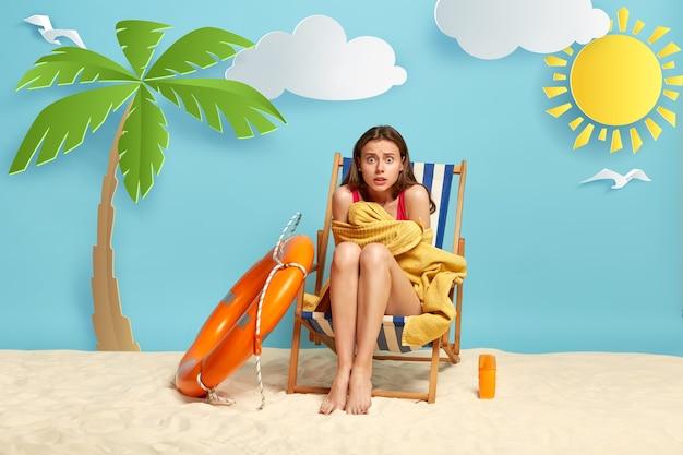 ショックを受けた素敵な女性は、海で泳いだ後、寒さを感じ、サンチェアに座って、タオルに包まれて震えます