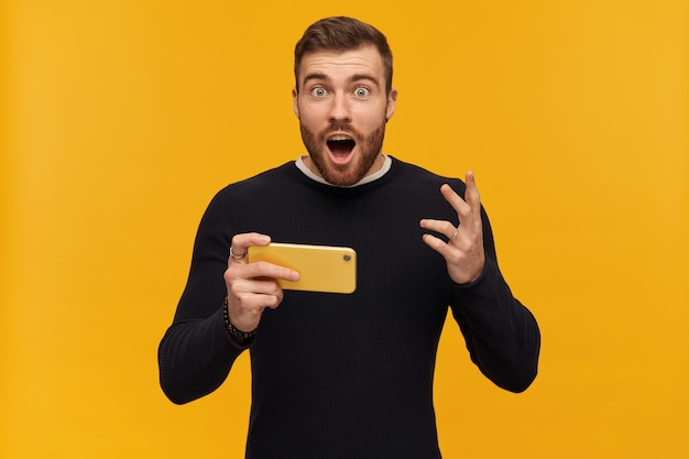 Shocked male, amazed guy with brunette hair and beard. has piercing. wearing black sweater. holding a smartphone. can't believe he won.  isolated over yellow wall