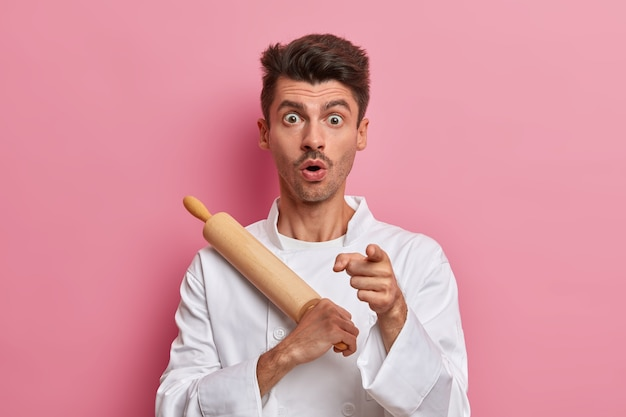 Shocked male baker holds rolling pin and points at front, gets ready to cook, works in kitchen, wears uniform
