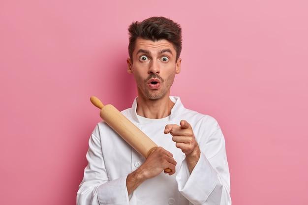 Il fornaio maschio scioccato tiene il mattarello e indica davanti, si prepara a cucinare, lavora in cucina, indossa l'uniforme