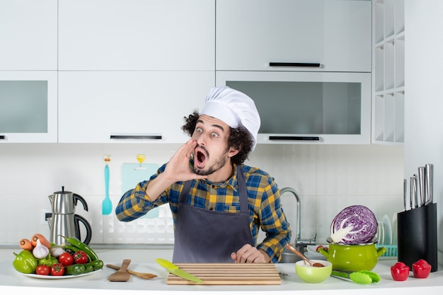 新鮮な野菜とキッチンツールで調理し、白いキッチンで誰かを呼び出すとショックを受けた男性シェフ