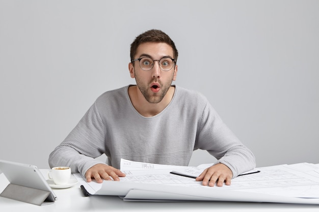 Shocked male engineer develops new image design, looks with opened mouth as remembers about important meeting
