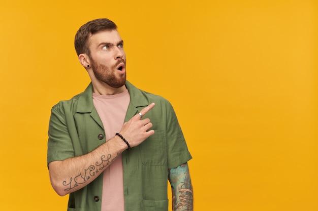 갈색 머리와 수염을 가진 충격을받은 남성, 찡그린 남자. 녹색 반팔 재킷을 입고. 문신이 있습니다. 노란색 벽 위에 절연 복사 공간에서 오른쪽을보고 손가락을 가리키는