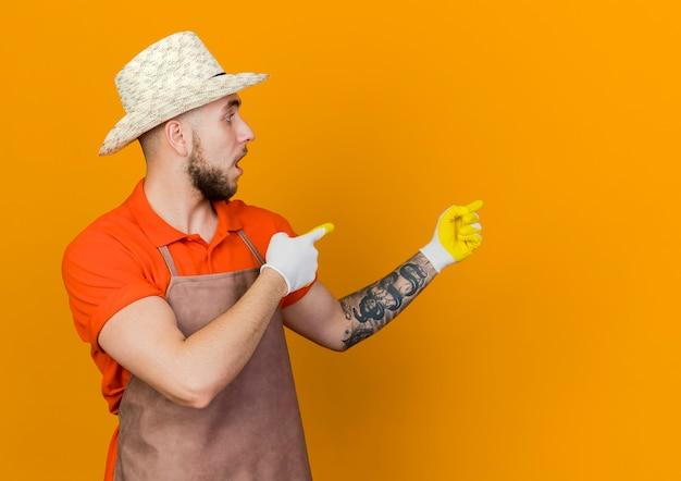 ガーデニングの帽子と手袋を身に着けているショックを受けた男性の庭師は、横に見えるとポイント