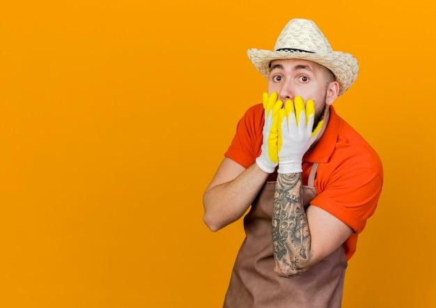 ガーデニングの帽子と手袋を着用してショックを受けた男性の庭師が口に手を置く