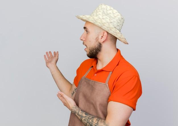 ガーデニング帽子をかぶったショックを受けた男性の庭師は、両手で横を見て後ろを指しています