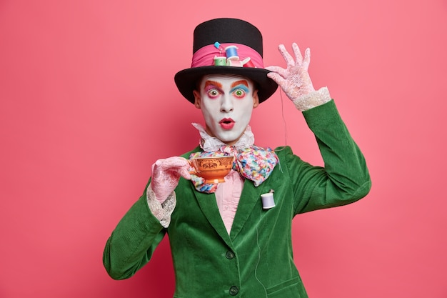 Shocked male has image of mysterious hatter from wonderland wears bright makeup poses with cup of tea dressed in aristocratic clothes isolated on pink wall