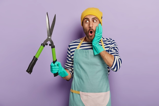 Shocked male professional gardener looks with great surprisement at sharp pruning shears
