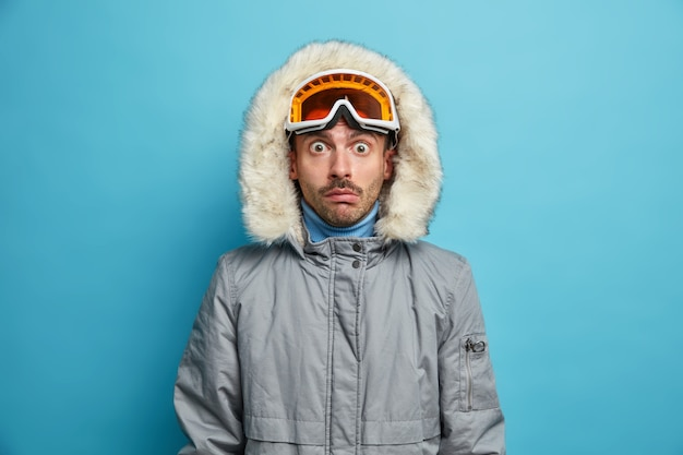 Shocked male skier wears ski goggles and warm winter jacket stares with bugged eyes has active rest in mountains during vacation.