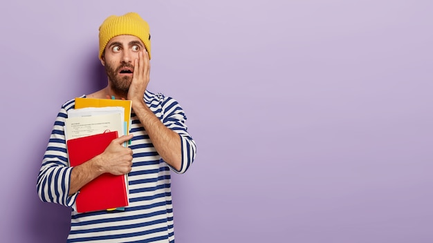 Shocked male student looks with terrified expression, keeps hand on cheek, carries notepad and papers, going to study, dressed in casual clothing stands indoor over violet wall