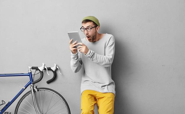 충격적인 남성, 유행 안경, 노란 바지와 스웨터를 입고 새 자전거를 사고 싶을 때 태블릿에서 놀랍게도 상점에서 높은 가격에 놀랐습니다.