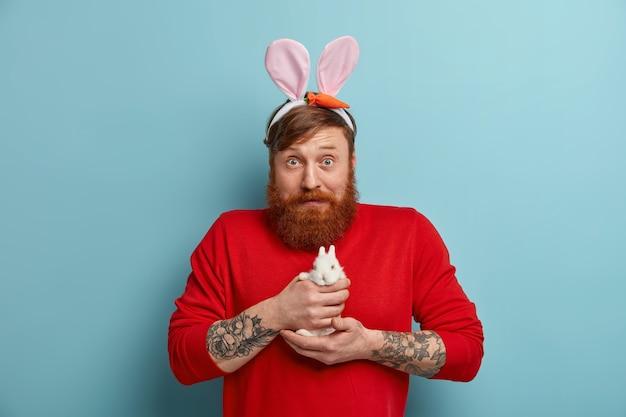 Шокированный самец с кроличьими ушками держит маленького кролика, готовится к празднику пасхи