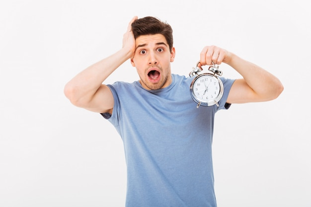 Shocked man 30s with brown hair holding alarm clock and grabbing head while being late, isolated over white wall
