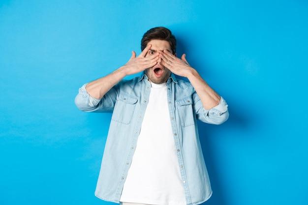Uomo scioccato che copre gli occhi e sbircia tra le dita, fissa qualcosa di imbarazzante, in piedi su sfondo blu.