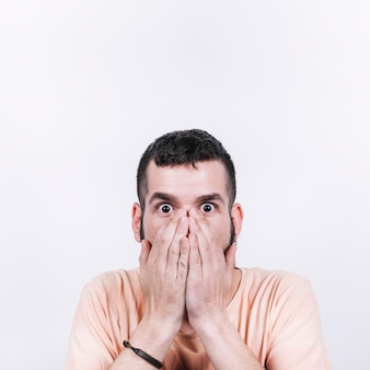 Shocked man covering mouth and looking at camera