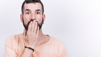 Shocked man covering mouth