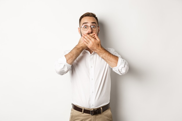Shocked man gasping and looking at something in awe, covering mouth with hands, white background.
