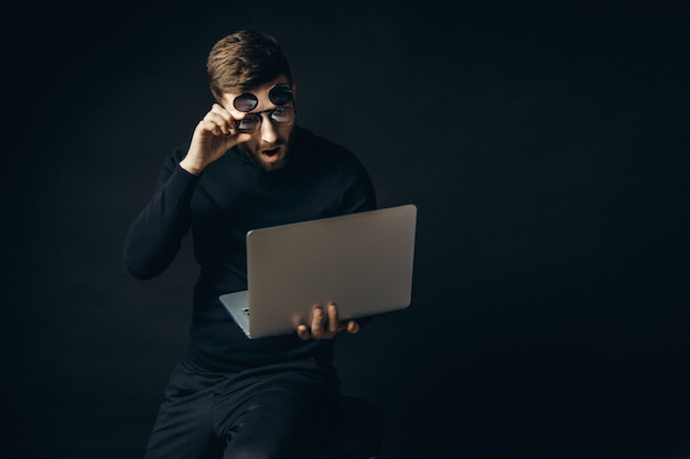 Shocked man in glasses looking at laptop