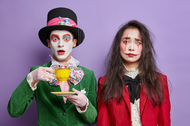Shocked man has image of mad hatter spends free time on tea party stares surprised wears professional makeup