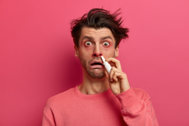 Shocked man has red swollen eyes, splashes nose drops, cures allergic rhinitis, has home treatment, stares , poses against pink wall drips medication inside. symptoms of cold or allergy