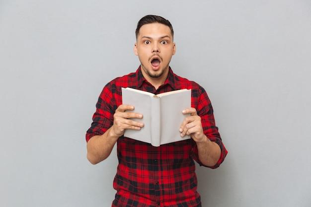 손에 책을 들고 충격 된 남자