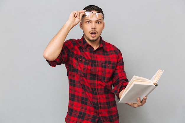 Shocked man holding book