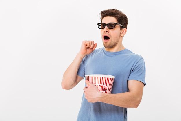 Шокированный мужчина в футболке и 3d-очках ест попкорн из ведра и смотрит в сторону серой стены