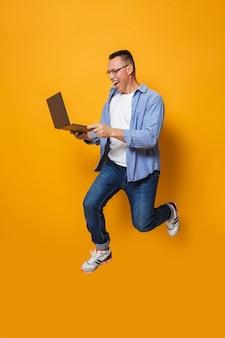 Потрясенный человек прыгает изолированно через желтую стену с помощью портативного компьютера.