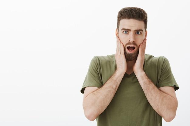 Uomo scioccato che apprende notizie terribili o voci che si diffondono in ufficio tenendosi per mano sulle guance ansimando e lasciando cadere la mascella in agitazione essendo senza parole e sconvolto o notizie sul muro bianco