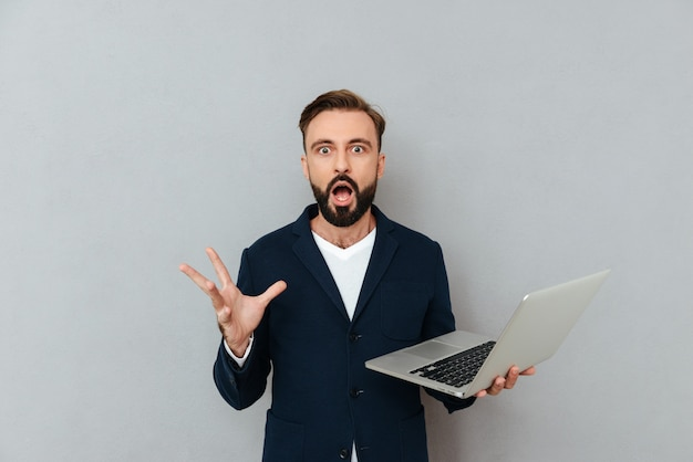 Shocked man looking camera while holding laptop computer