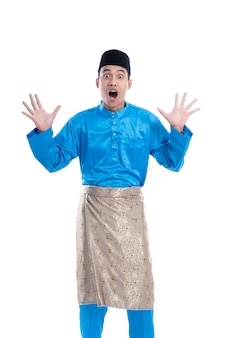 Shocked man looking at camera over white background. male with satin melayu clothes