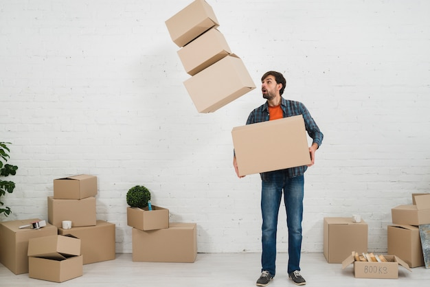 Shocked man looking at the fallen moving cardboard boxes