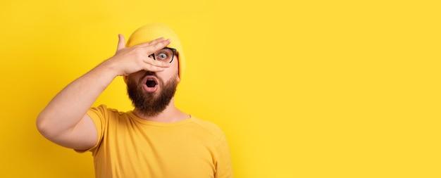 노란색 배경 위에 손가락을 통해 보고 충격을 받은 남자, 텍스트를 위한 공간이 있는 탁 트인 레이아웃