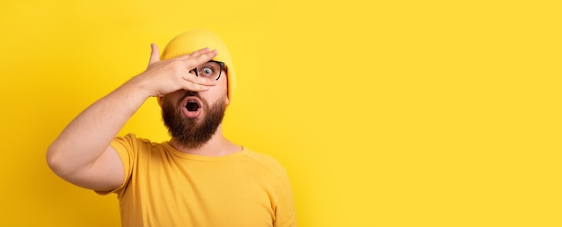 Shocked man looking through fingers over yellow background, panoramic layout with space for text