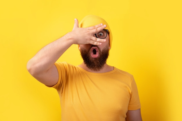Shocked man looking through fingers over yellow background