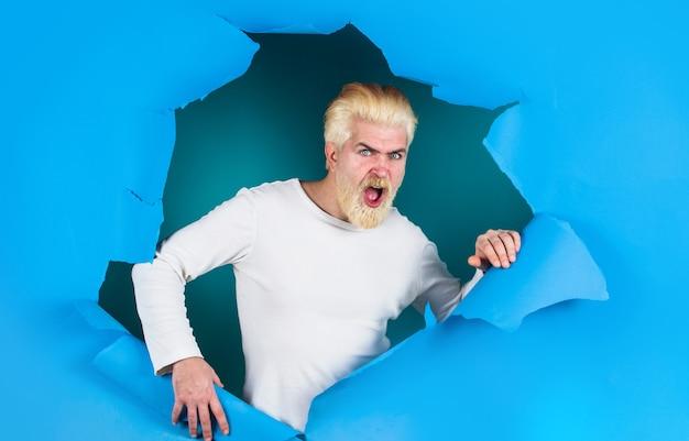 穴を通して見ているショックを受けた男。紙に穴を開けて驚いたひげを生やした男。ディスカウント、セール、シーズンセール。