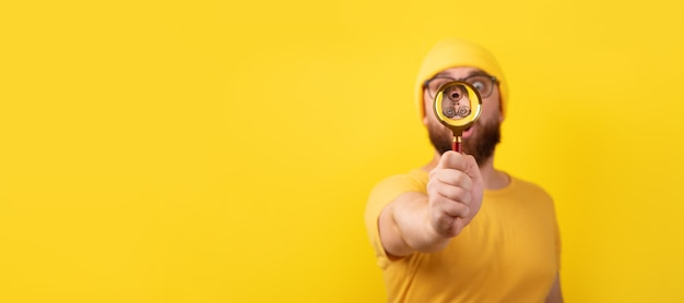 Shocked man looking through magnifier glass over yellow background, panoramic image