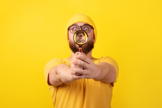 Shocked man looking through magnifier glass over yellow background