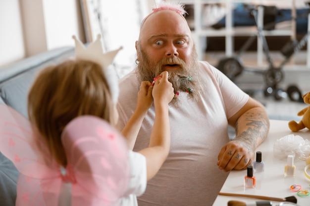 Шокированный мужчина сидит в комнате, пока дочь в костюме феи кладет резину ему на бороду