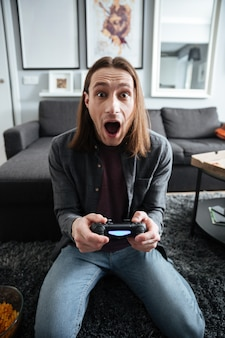 Shocked man sitting at home indoors play games with joystick