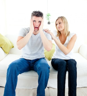 Shocked man sitting on the sofa with his girlfriend