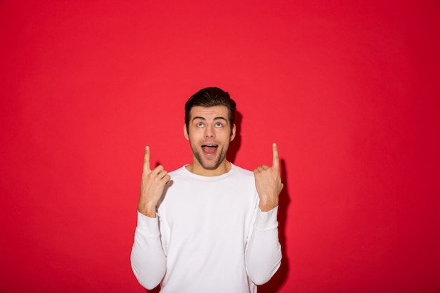 Shocked man in sweater pointing and looking up with open mouth over red wall