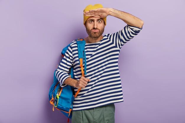 ショックを受けた男の旅行者は目を飛び出し、遠くに何か奇妙なものを見て、バックパックを運ぶ