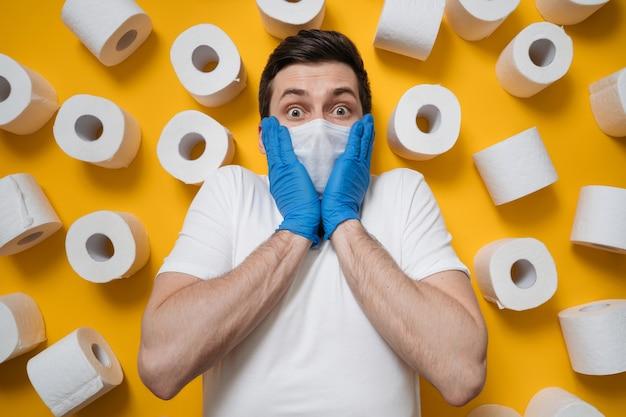 Шокированный мужчина в медицинской защитной маске от коронавируса окружен туалетной бумагой
